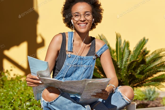 Cheerful happy African American lady enjoys tour in city, holds map for searching new places of inte