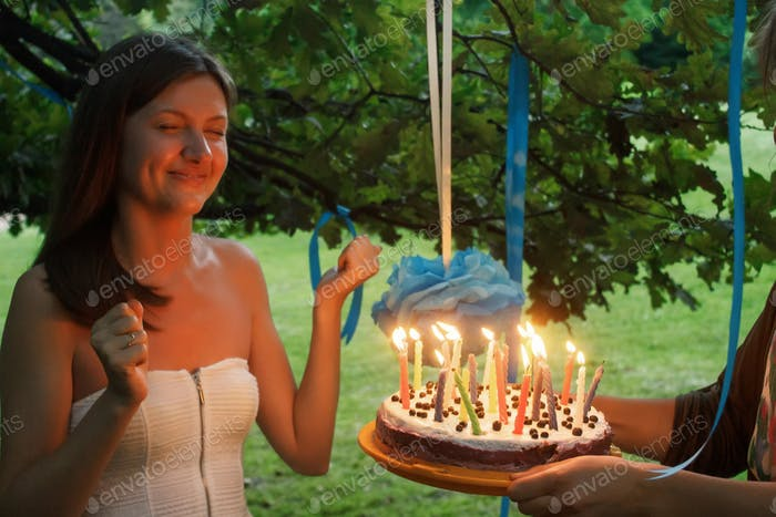 glückliche Frau macht einen Wunsch und blasen Kerzen auf Kuchen bei ihrer Braut Dusche im Sommerpark