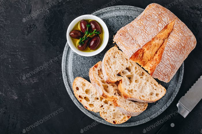 Italian ciabatta bread slices with olives on stone plate on dark concrete background