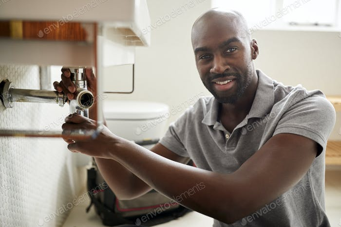 Young black male plumber sitting on the floor fixing a bathroom sink, looking to camera, close up