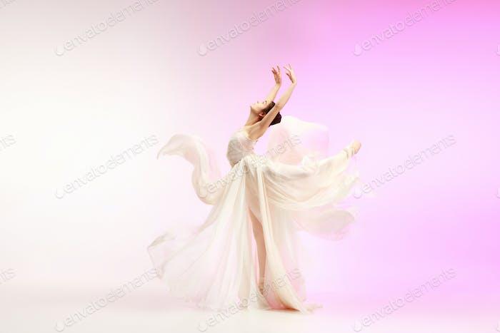 Ballerina. Young graceful female ballet dancer dancing over pink studio. Beauty of classic ballet.