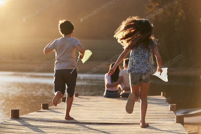 Children Run Towards Parents On Wooden Jetty By Lake