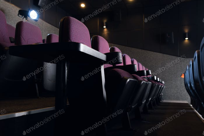 red seats in empty dark movie theater