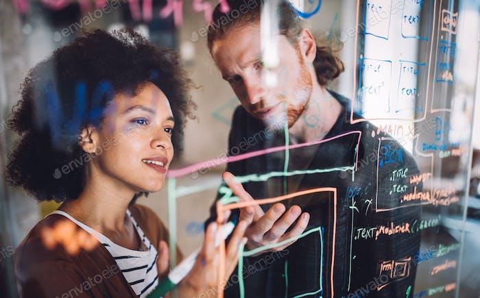 Programadores cooperan lluvia de ideas en empresa de tecnología de la información