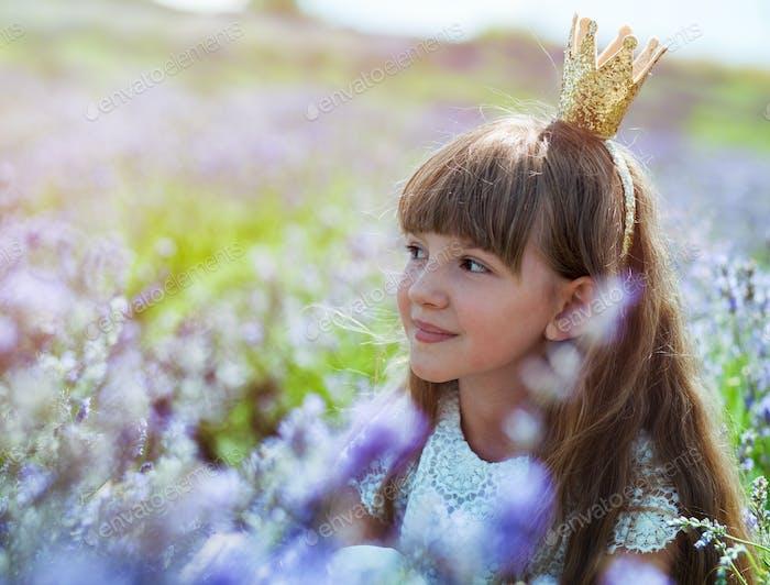Princesa niña niña en corona en el campo de lavanda en el día de verano, concepto de infancia feliz