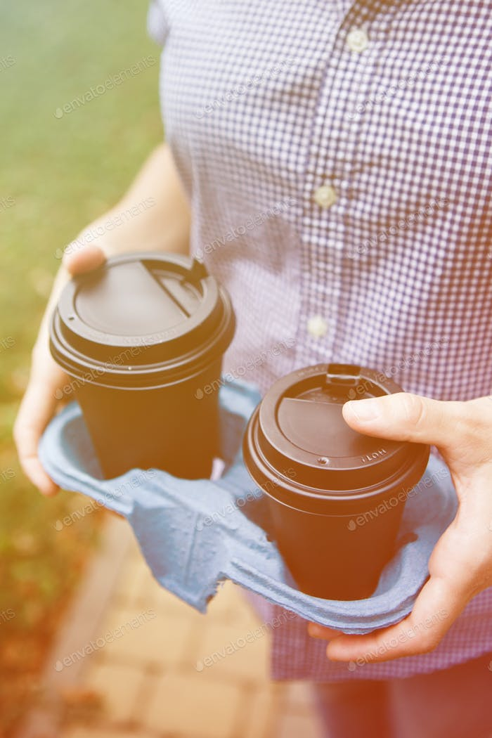 Crop person holding coffee cups