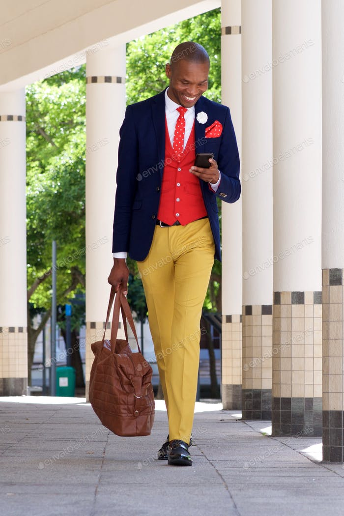 young businessman walking and reading text message on cell phone