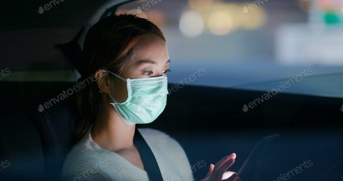 Mujer usa máscara facial médica y uso del teléfono celular en la ciudad por la noche