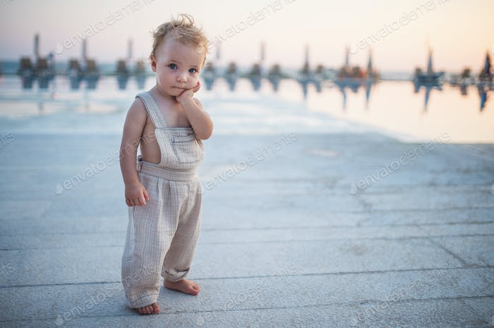 A small toddler girl standing on beach on summer holiday. Copy space.