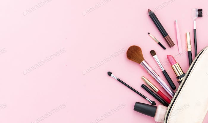 Make-up cosmetic bag against pink background, copy space