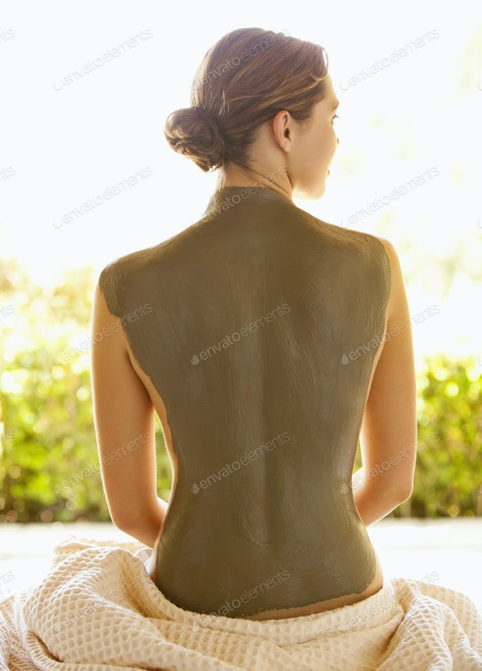 Caucasian woman with mud treatment on back