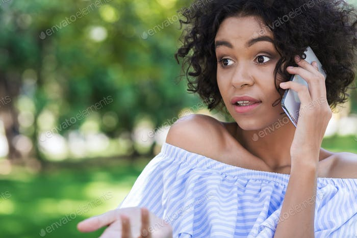 Young shocked woman talking on phone in park