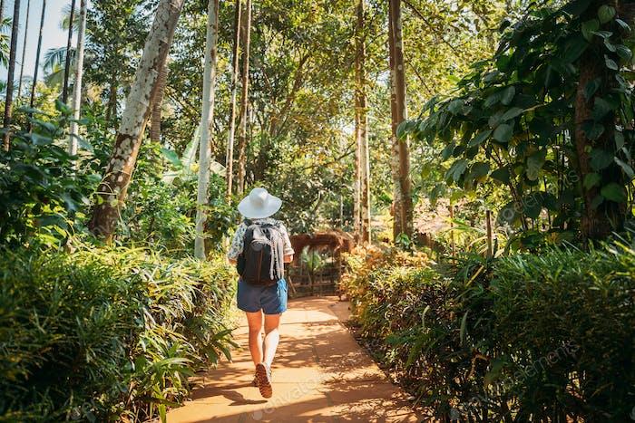 Goa, India. Young Backpacker Woman Walking Through Botanical Garden In Sunny Day
