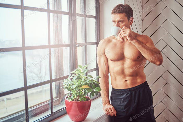 Handsome shirtless muscular male leaning on window sill, drink a cup of a coffee