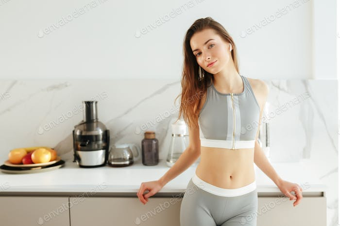 Beautiful lady in sporty top and leggings on kitchen in earphones dreamily looking in camera