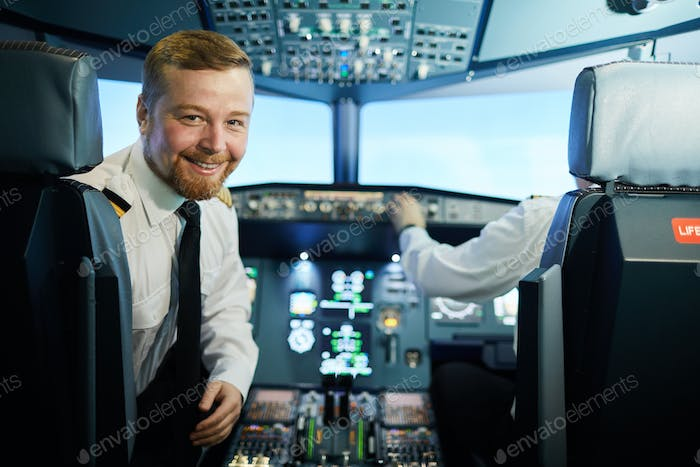Confident bearded pilot in cockpit