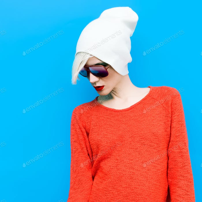 fashion blond girl with trendy cap and sunglasses on a blue back