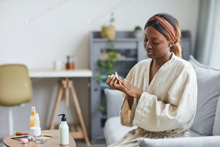 Young African American Woman Using Hand Cream
