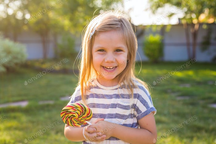 Funny child with candy lollipop, happy little girl eating big sugar candy.