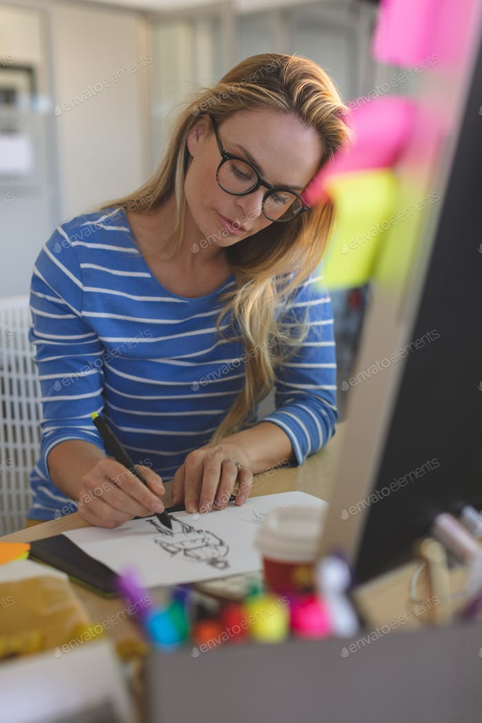 Young Caucasian blonde female fashion designer drawing sketches at desk in a modern office