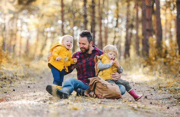 A mature father with toddler children sitting on the ground in an autumn forest.