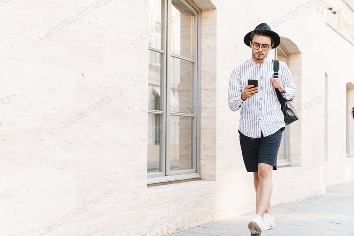 Photo of focused unshaven man typing on cellphone while walking in city street