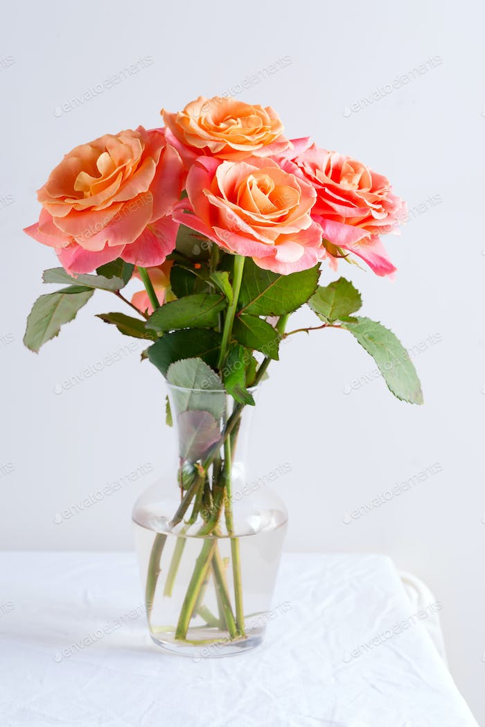 Glass vase with beautiful bouquet of fresh natural roses flowers on a table covered white cloth