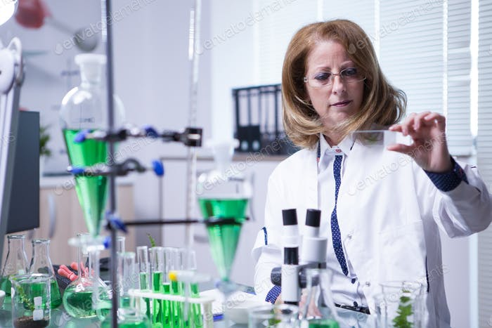 Женщина-ученый, выполняющий химический анализ на образце в лаборатории