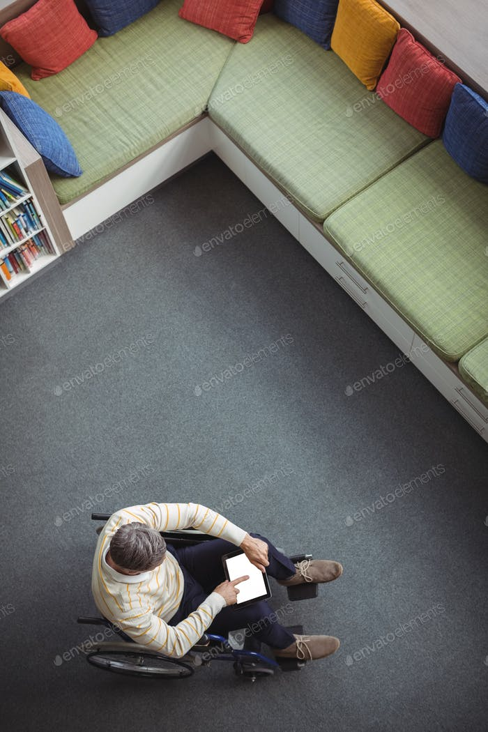 Overhead view of disabled school teacher using digital tablet in library