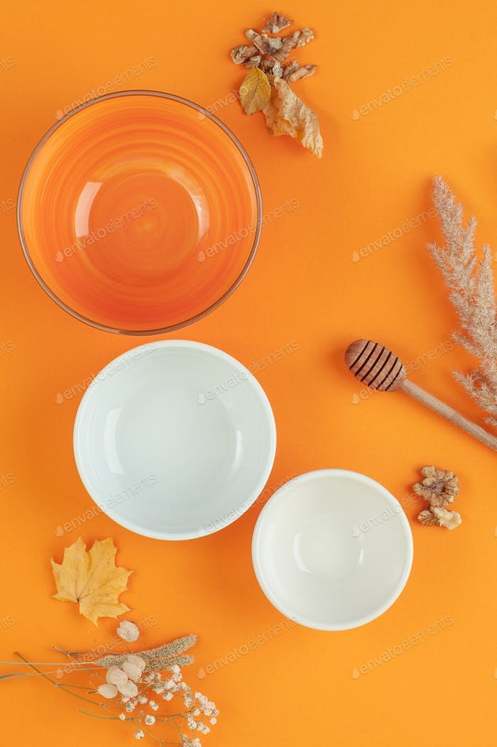 Three empty bowls of different sizes on a bright orange backgrou