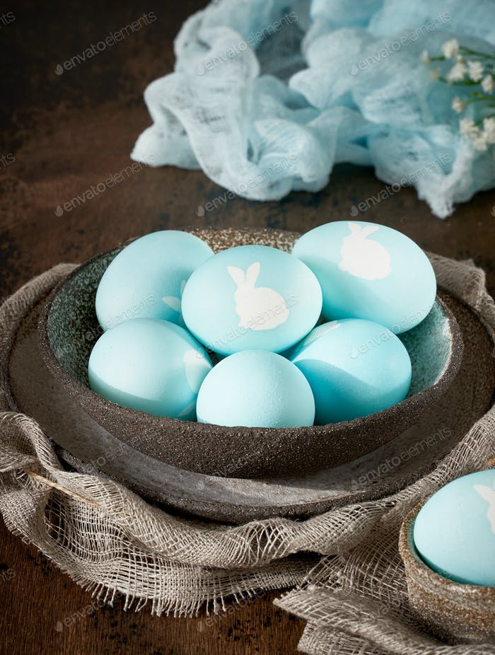 Unusual Easter on dark old background. Ceramic brown bowl with blue eggs. Darkness, rays of sunlight