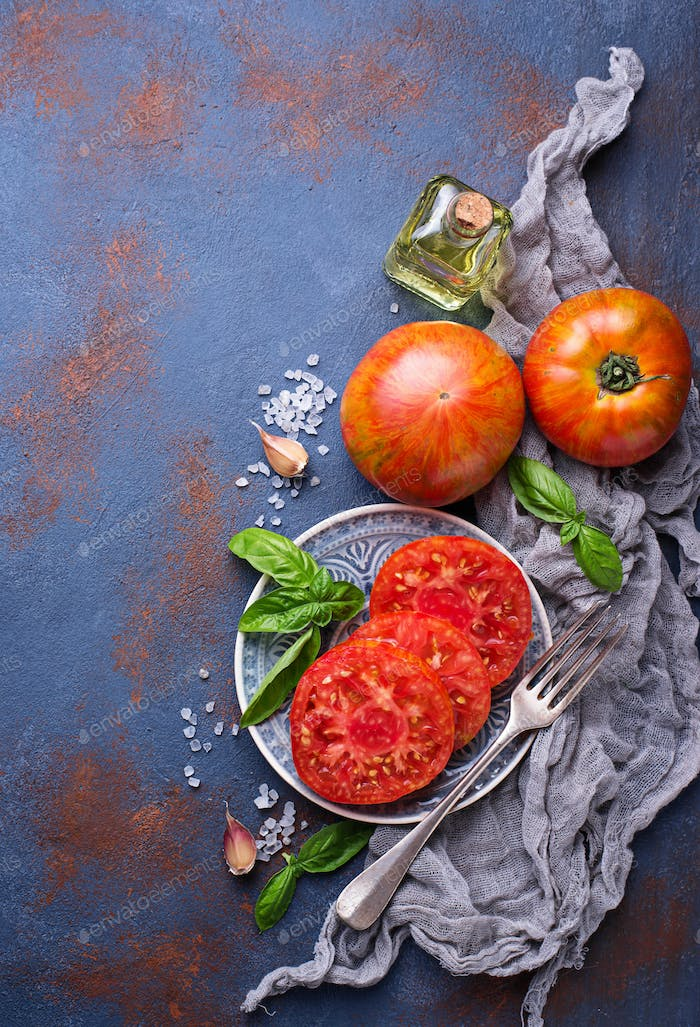 Sliced tomato on blue rusty background