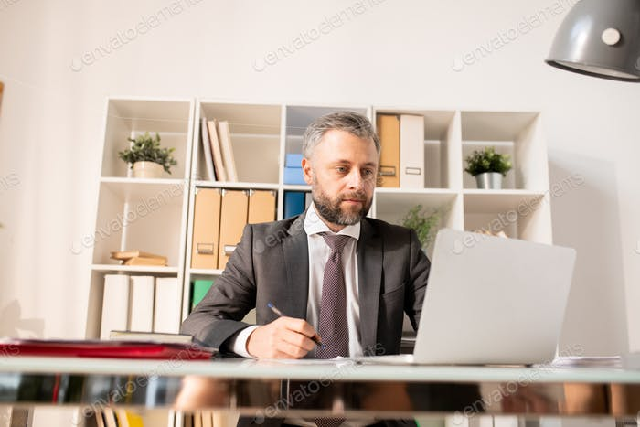 Busy man in suit analyzing information on laptop