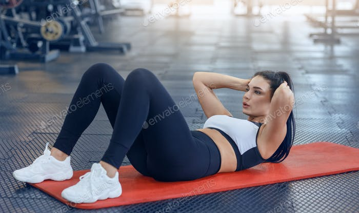 Strong young woman doing abs exercises on floor at fitness centre