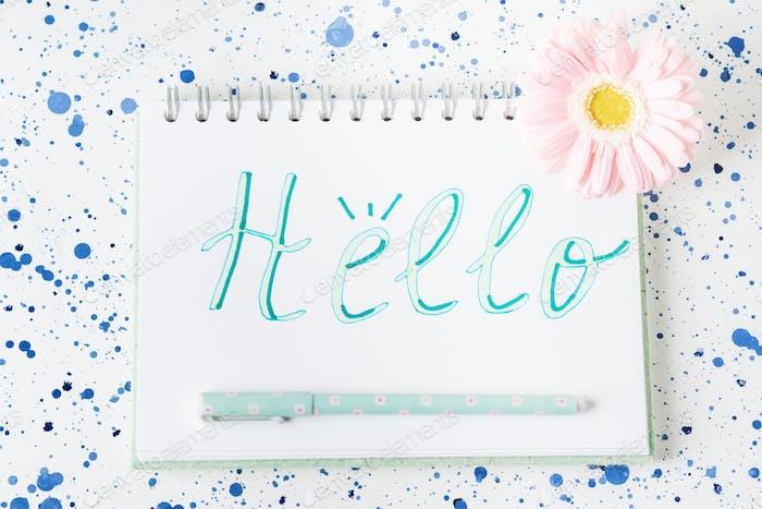 Hello word written on notepad page. Gerbera Flower