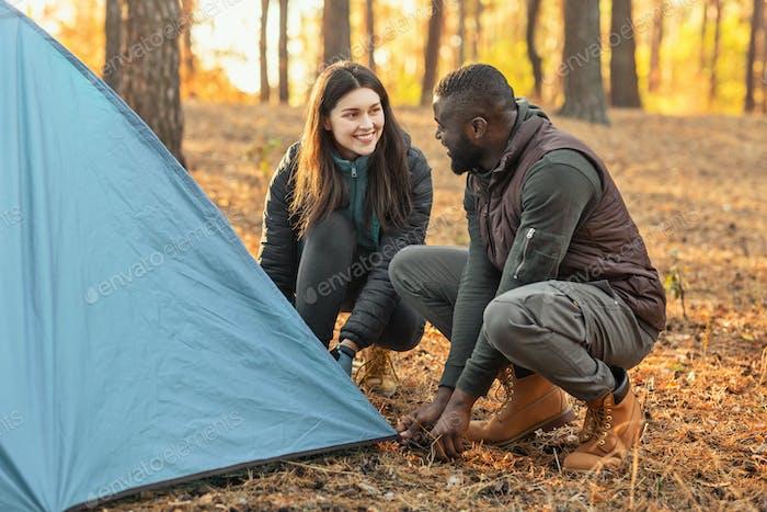 Mann und Frau machen Zelt zusammen, Gespräch