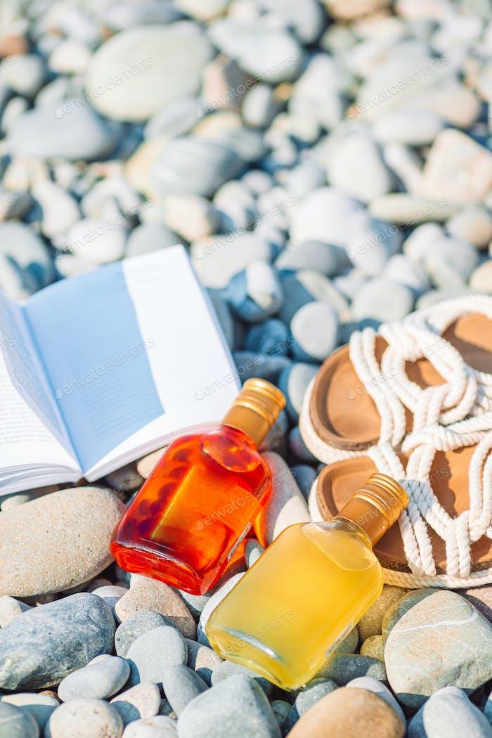 Strandhut auf geöffnetem Buch mit Sonnencreme und Schuhen am Kiesstrand