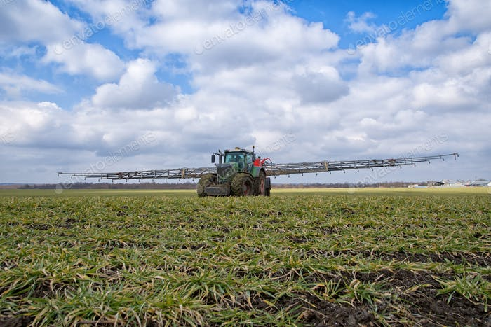 tractor spraying wheat