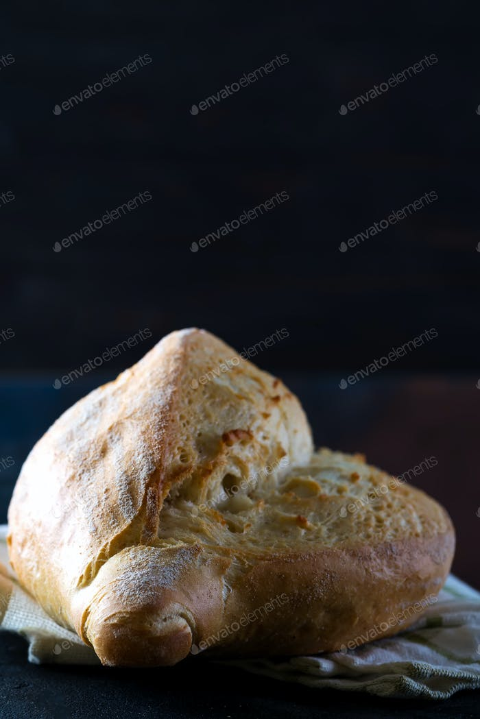 Homemade french bread with a napkin on a dark background, close-up