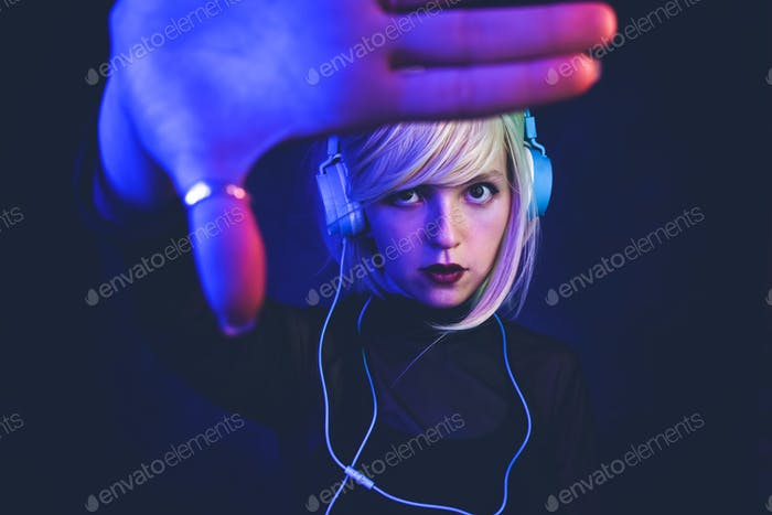 Young woman listening to music and illuminated by neon lights