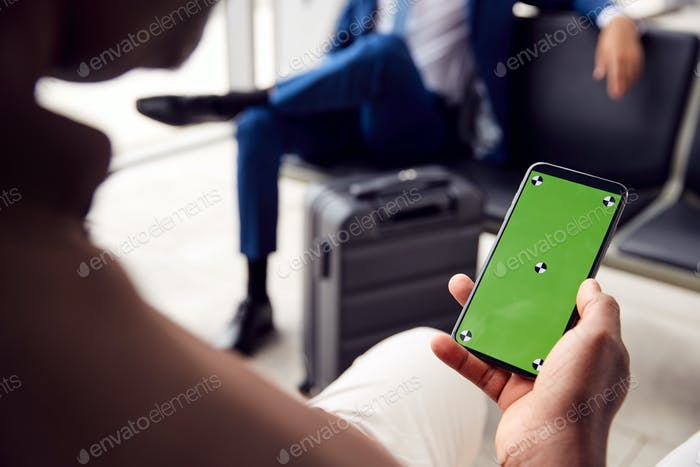 Male Passenger In Airport Departure Lounge Looking At Green Screen On Smart Phone
