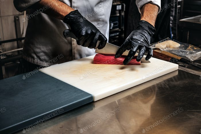 Close-up photo of a cook in uniform and gloves preparing sushi on cutting board in the kitchen.