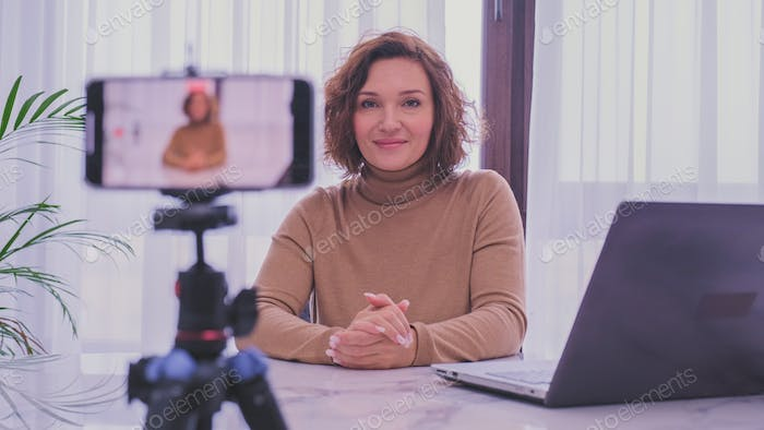 Smiling woman recording her video blog.