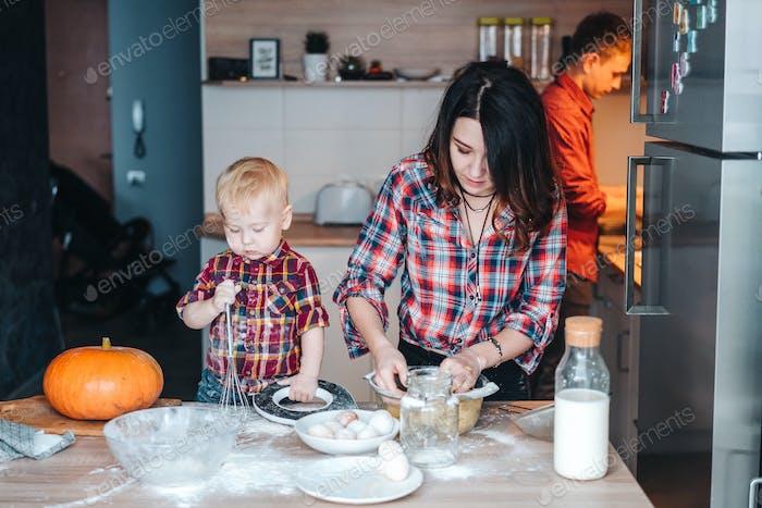 Papa, Mama und kleiner Sohn kochen einen Kuchen