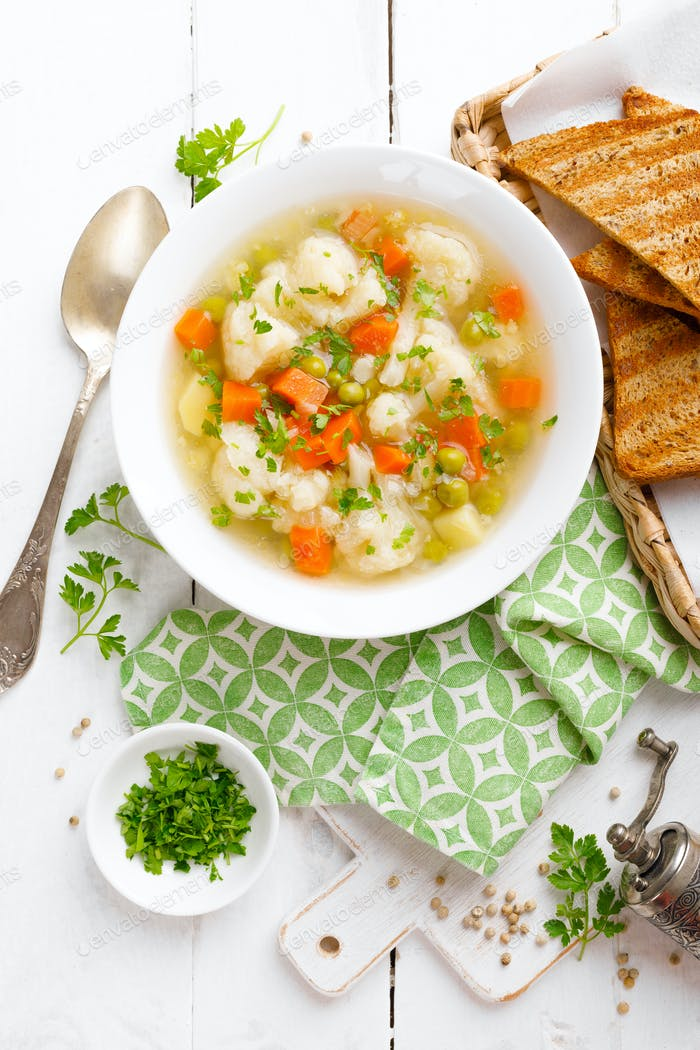 Vegetable soup with cauliflower, carrot, green peas, onion and potato