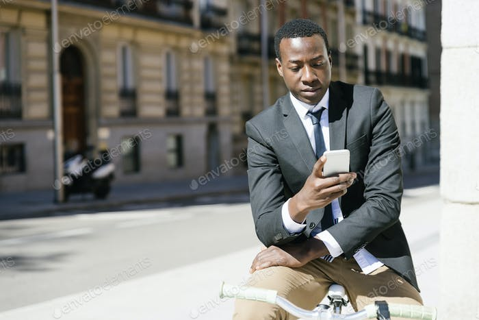 Handsome african man smiling when he is using his mobile.