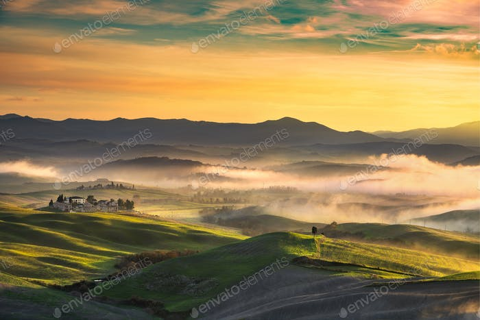 Volterra foggy panorama, rolling hills and green fields on sunse