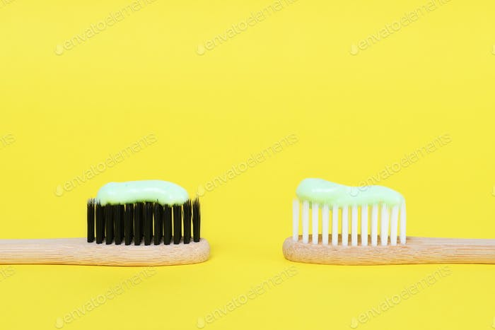 Bamboo toothbrushes with organic toothpaste on yellow background
