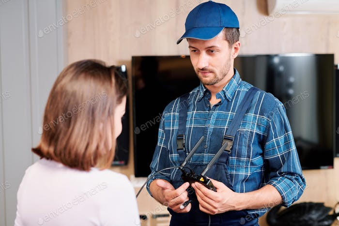 Repairman or technician in workwear pointing at household device