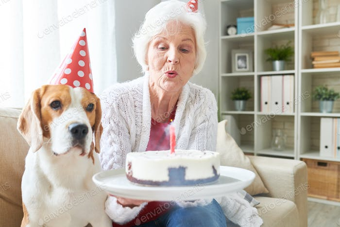 Senior Woman Blowing Birthday Candles
